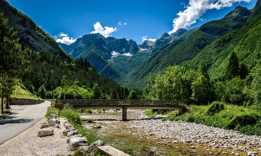 Idyllic mountain river in Lepena valley, Soca - Bovec Slovenia. Bridge over of river Lepenca when heading towards Sunik water grove. Beautiful landscape scene with forest, mountains and river in Slovenia, Europe. Green Green Color Lepena Lepenca Nature Riverside Slovenia Soca River Sunik Water Grove Trees Alps Beauty In Nature Bovec Bridge Forest Julian Alps Mountain Nature River Soca Stream Torquoise Valley Waterfall Woods