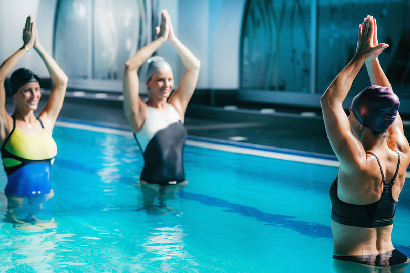 Swimmers with arms raised exercising in swimming pool