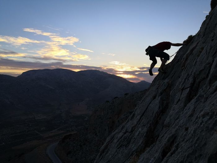 Side view of man rope climbing mountain against sky during sunset