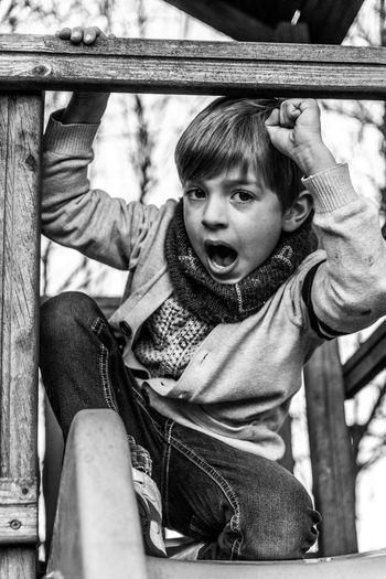 Portrait of boy sitting on railing