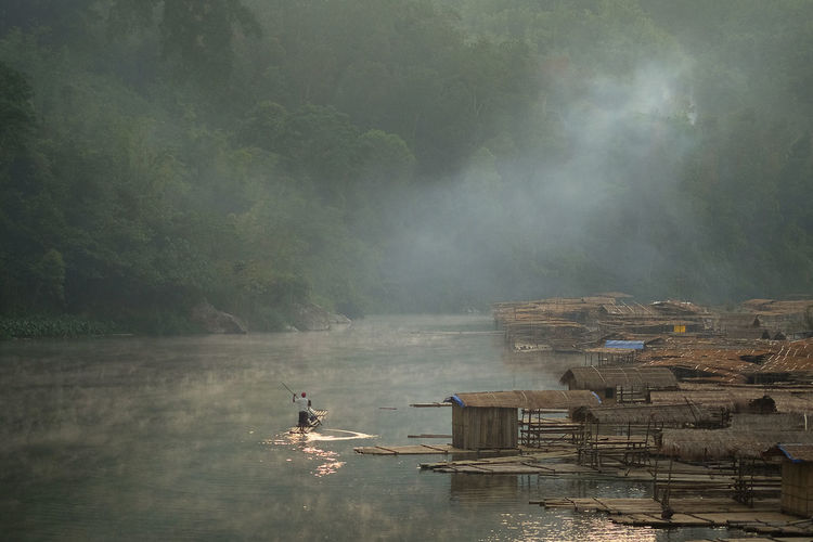 Man sailing wooden raft in river during foggy weather