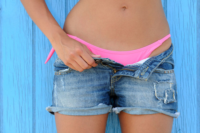 Midsection of woman removing shorts against wooden wall
