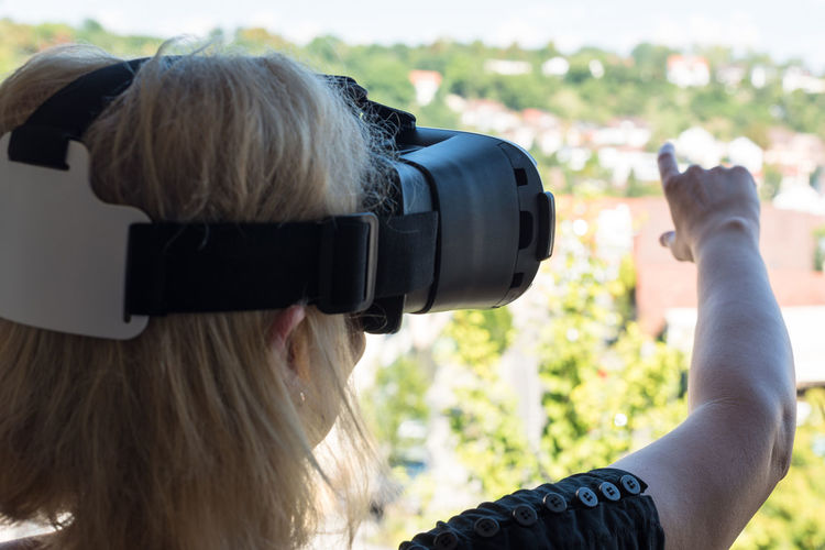 Rear view of woman with virtual reality simulator
