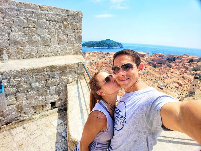 Portrait of young couple kissing against blue sky