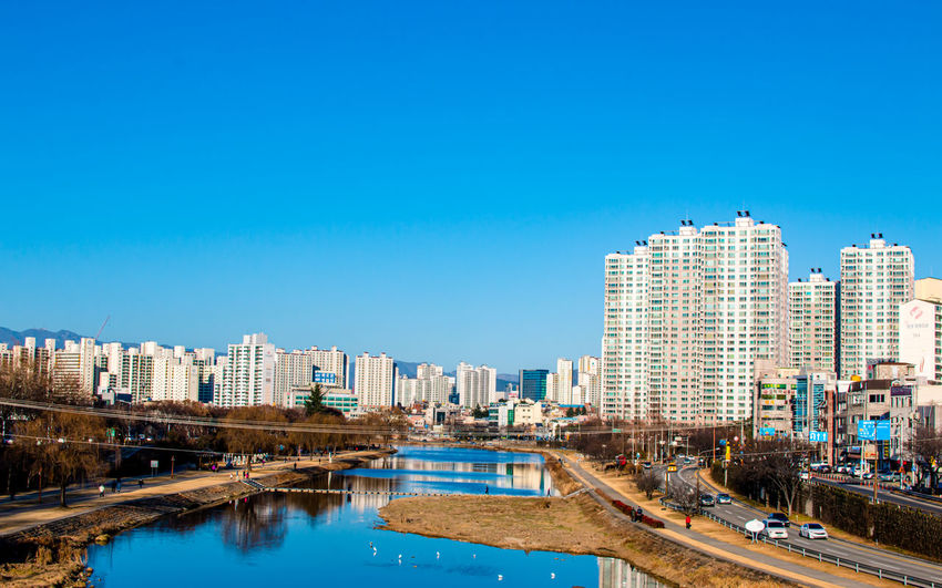 Canal amidst buildings against clear blue sky