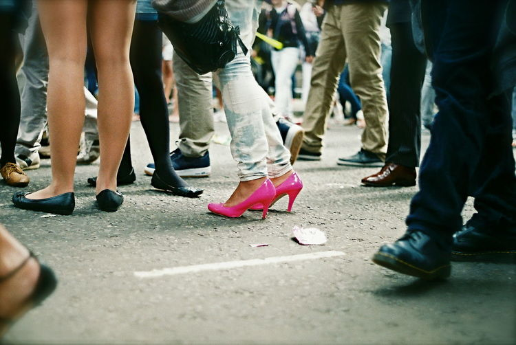 Casual Clothing City Life Crowd Crowded Crowded Street Day Focus On Foreground Footwear Heels Human Foot Isolated Leisure Activity Lifestyles Low Section Medium Group Of People Outdoors Part Of Person Pink Selective Focus Shoes Stand Out From The Crowd Standing Standing Woman