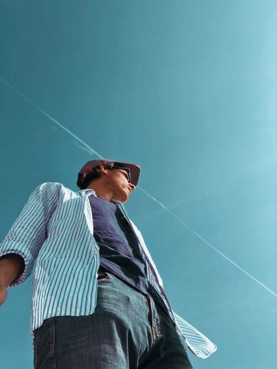 Low angle view of man looking away while standing against blue sky