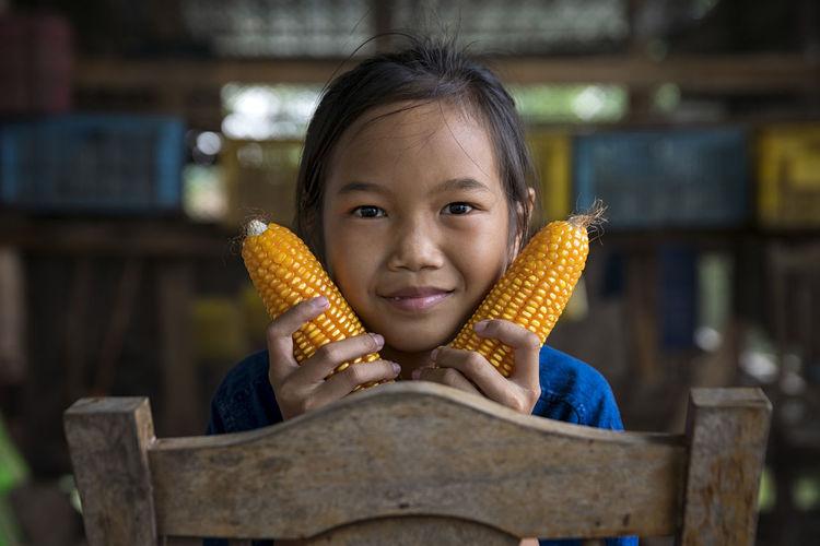 Portrait of girl holding sweetcorn