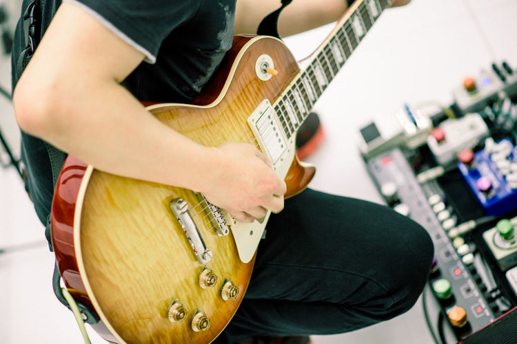 Midsection of man playing guitar at recording studio