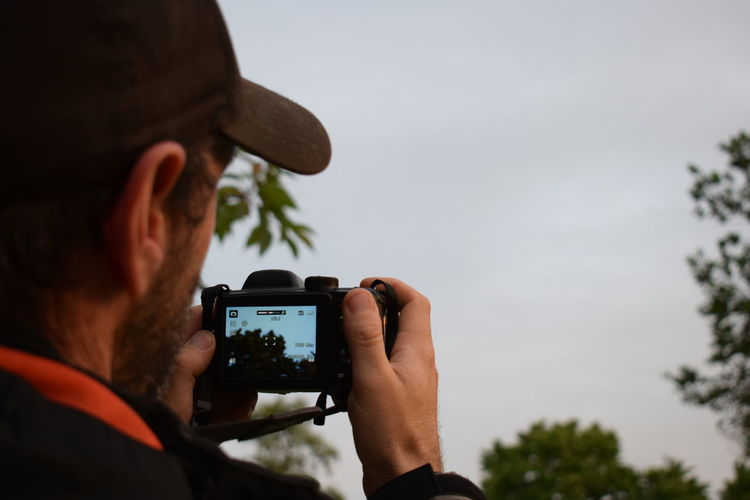 Rear view of man photographing through camera against sky