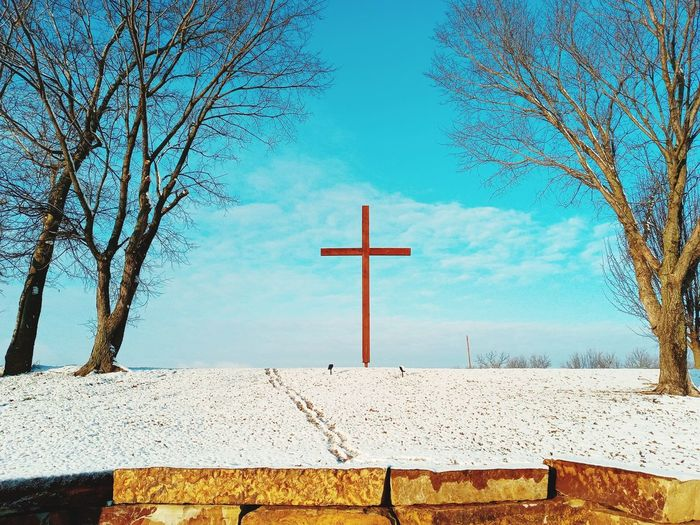 Cross on field against sky during winter
