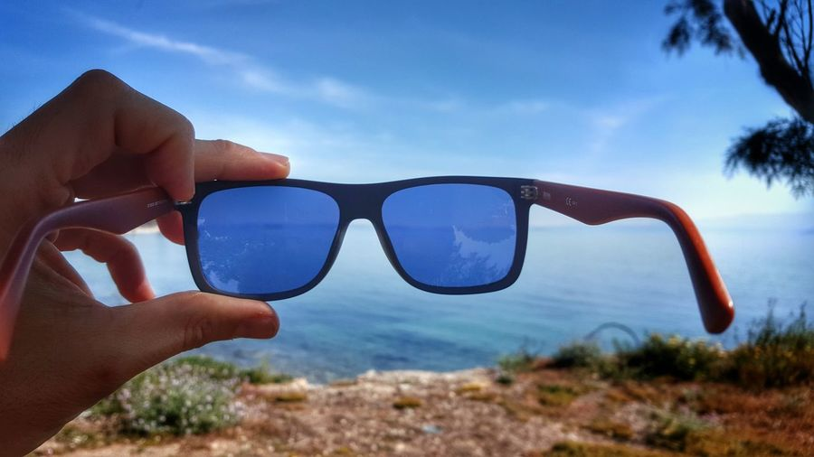 Close-Up Of Person Holding Sunglasses Against Sea
