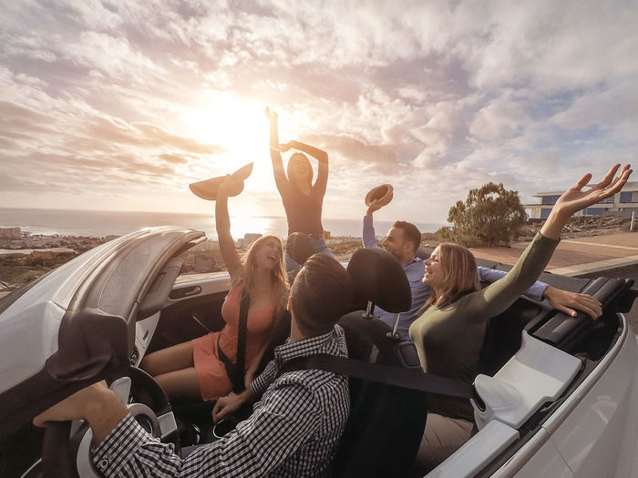 Friends driving on convertible car Car Convertible Cabrio Cabriolet People Holidays Vacation Mode Of Transportation Group Of People Transportation Sky Real People Friendship Women Motor Vehicle Adult Lifestyles Togetherness Travel Sitting Nature Emotion Arms Raised Road Trip Outdoors