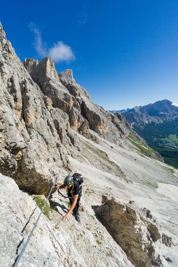 High angle view of woman climbing on mountain against blue sky