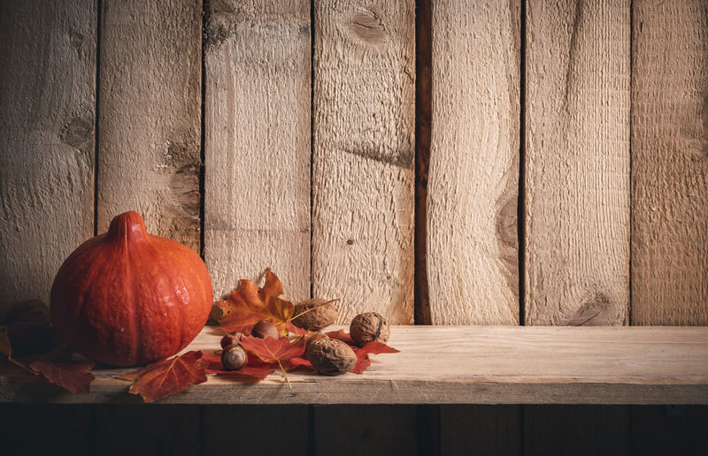 Autumn frame with an orange pumpkin surrounded by red leaves, walnuts, and hazelnuts, on a shelf against a vintage wooden background. Autumn Collection Autumn Leaves Celebration Chestnuts Event Halloween Holidays Rustic Thanksgiving Brown Decoration Fall Leaves Family Time Food Leaf Pumpkin Still Life Vegetable Wallnuts Wooden Background Wooden Shelf