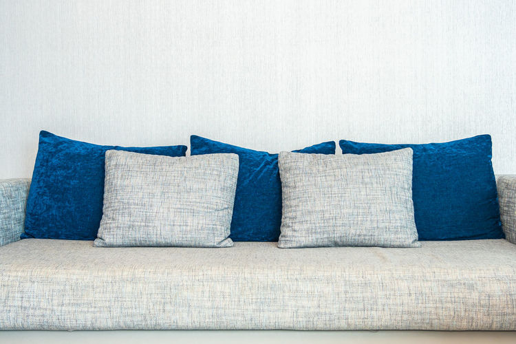 Close-up of sofa against blue wall at home
