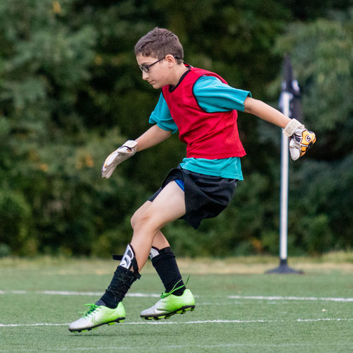Full length of boy playing soccer on grass