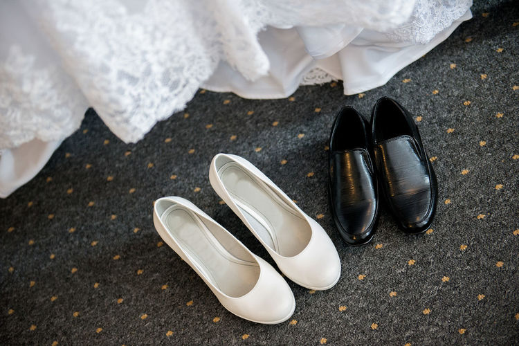 High angle view of shoes on carpet by wedding dress