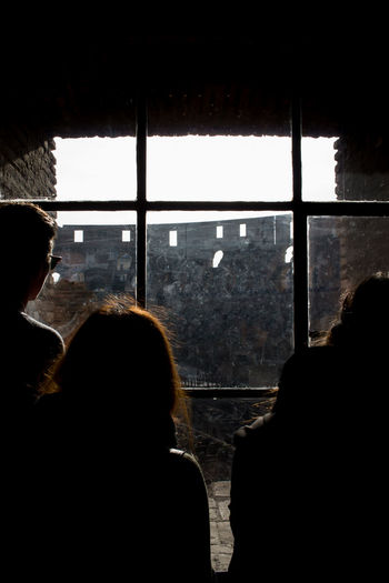 Silhouette people looking through window