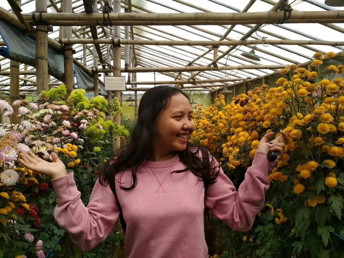 Beautiful young woman standing in greenhouse