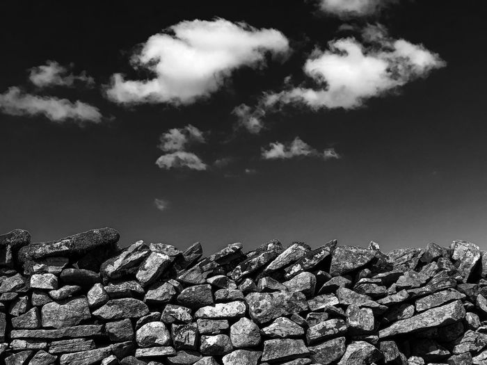 Low angle view of stack of stones against sky