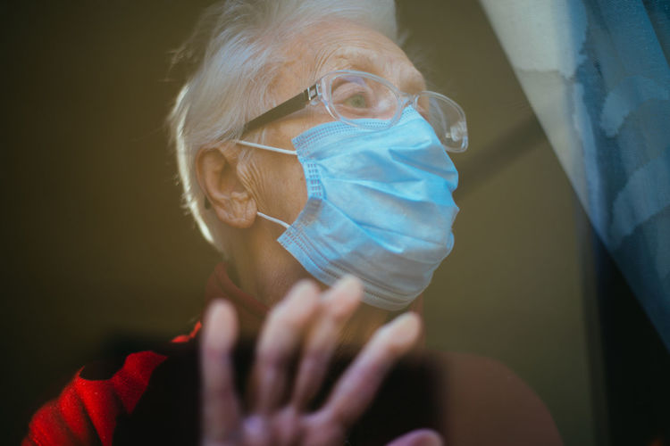 Close-up of senior woman wearing mask seen through window