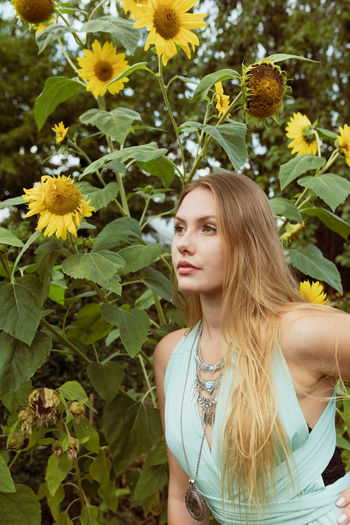 Young woman looking away while standing against flowering plants
