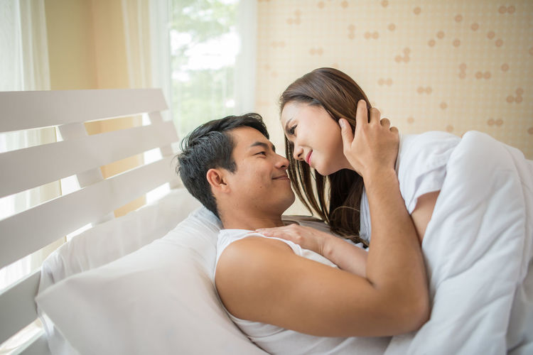Couple cuddling on bed at home