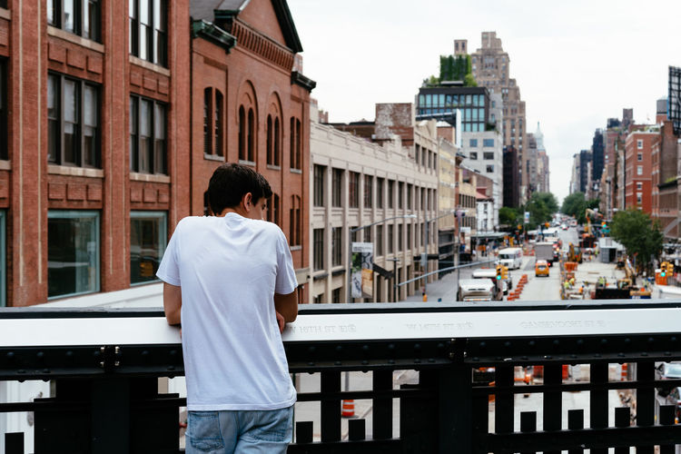 Young looking at cityscape of Chelsea, NY Chelsea City Cityscape High Line Park Adult Architecture Building Building Exterior Built Structure Casual Clothing City City Life Day Leisure Activity Lifestyles Men Millennials Nature One Person Real People Rear View Standing Three Quarter Length Transportation Young Adult