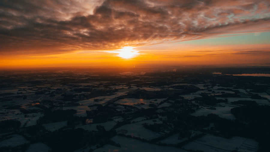 Aerial view of landscape against dramatic sky during sunset