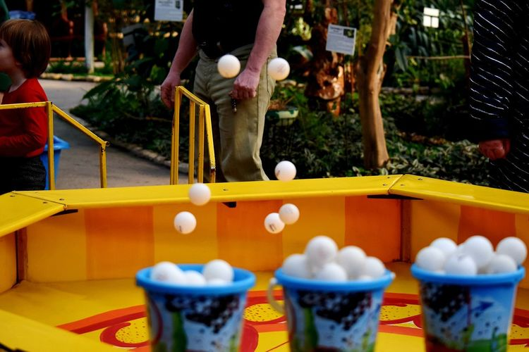 Balls in bucket and mid-air with man standing in background