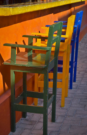 Barstools lined up at a cafe in Isla Mujeres, Mexico Absence Arrangement Bar, Travel, Tourism, Isla Mujeres, Mexico, Bright, Colorful, Vivid Barstools Cafe Carribean Chair Day Empty Furniture In A Row No People Orange Color Restaurant Seat Table Wood - Material Yellow