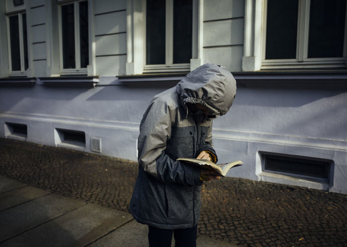 Man reading book while standing on footpath