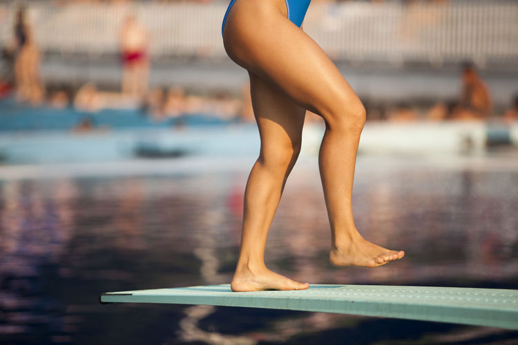 Female diver standing on a springboard, preparing to dive into a swimming pool Diving Holiday Jump Recreation  Swimming Dive Diver Diving Board Feet Girl Hotel Human Leg Jumping Leisure Activity Lifestyles Outdoors Sport Springboard Summer Swimmer Swimming Pool Vacation Water