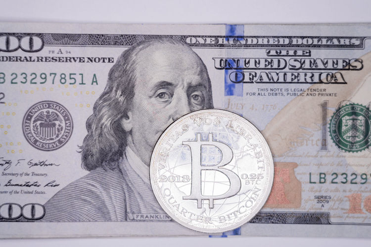 Bitcoin sitting on top of one hundred dollar bill 100 Dollar Bills American Benjamin Franklin Bills Bitcoin Buying Cash Compensation Currency Digital Fraud Management One Hundred Pay Payday Payment Salary Selling Tax Wages Wallet Wealth