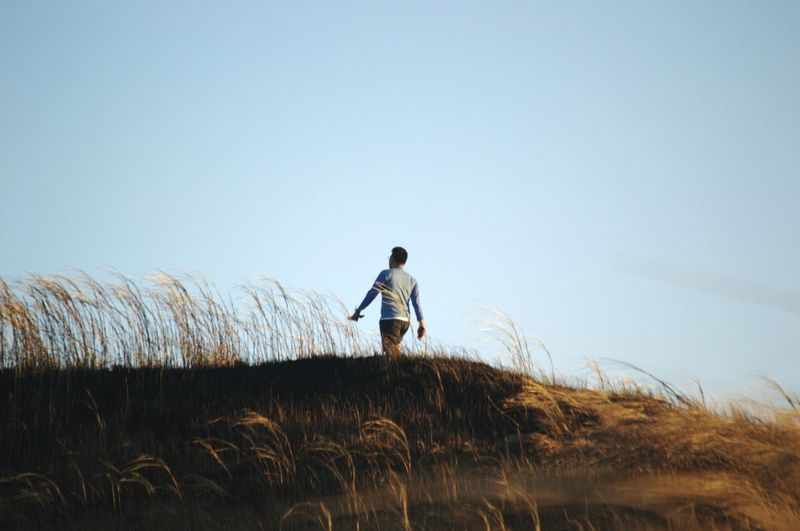 Low angle view of man walking on hill against clear sky