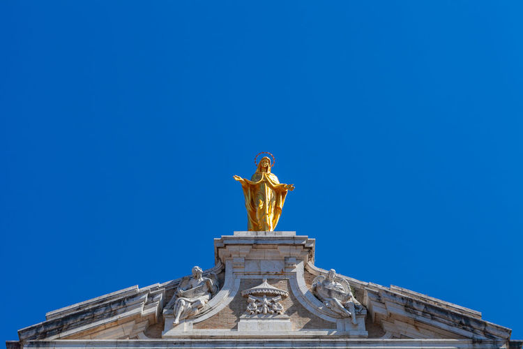 Golden madonna sculpture on top of santa maria degli angeli basilica, assisi, italy