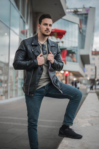Young man looking away while standing in city