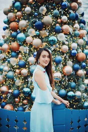 Portrait of smiling young woman standing by christmas tree outdoors