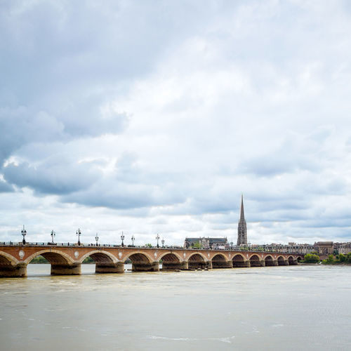 Arch bridge over river by church against cloudy sky in city
