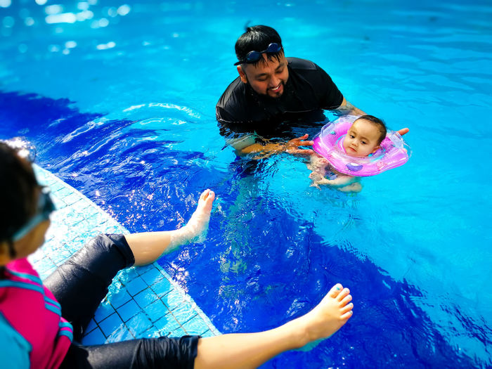 Father Swimming With Children In Pool
