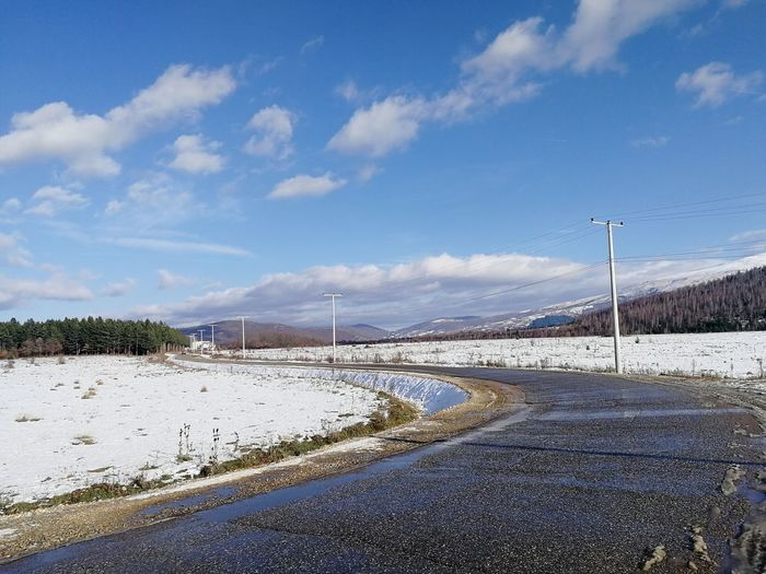 Road by snow covered landscape against sky