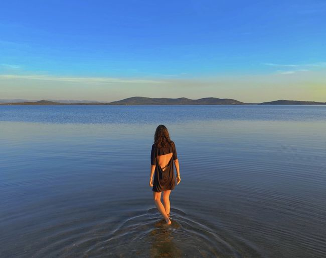 Woman standing in sea against sky