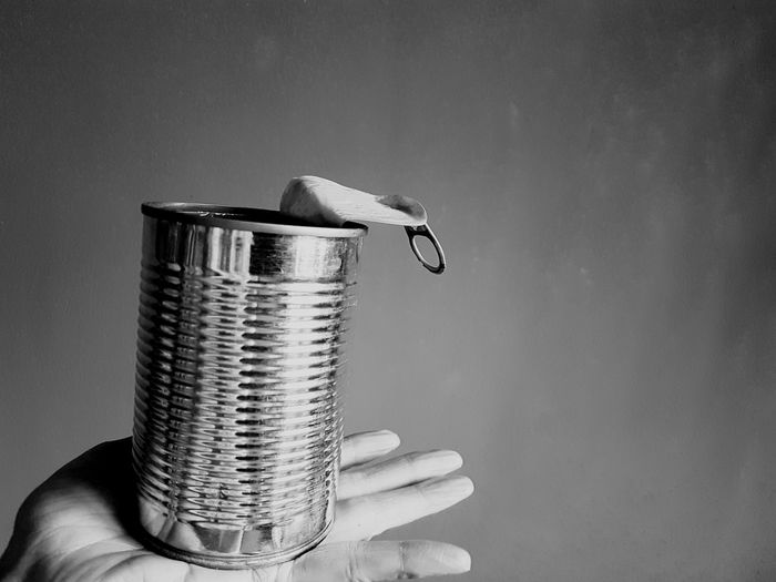 Close-up of hand holding tin can against wall