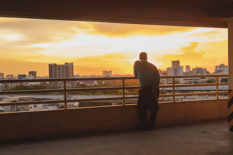 Rear view of man standing by railing against sunset sky