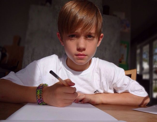 Close-up portrait of a boy writing at table
