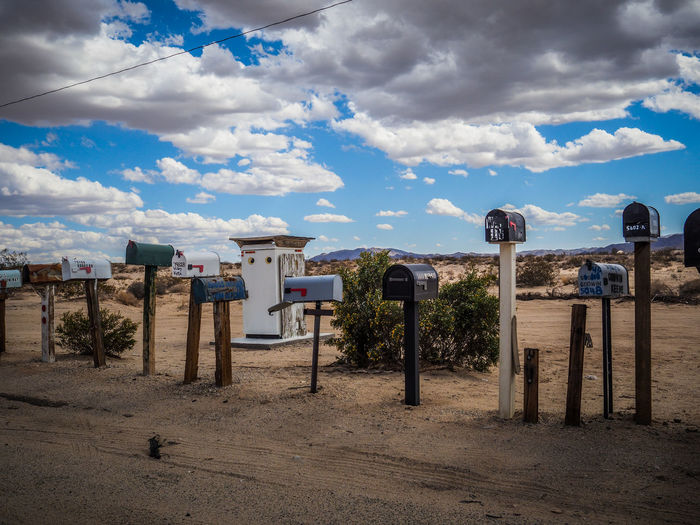 Mailboxes against cloudy sky