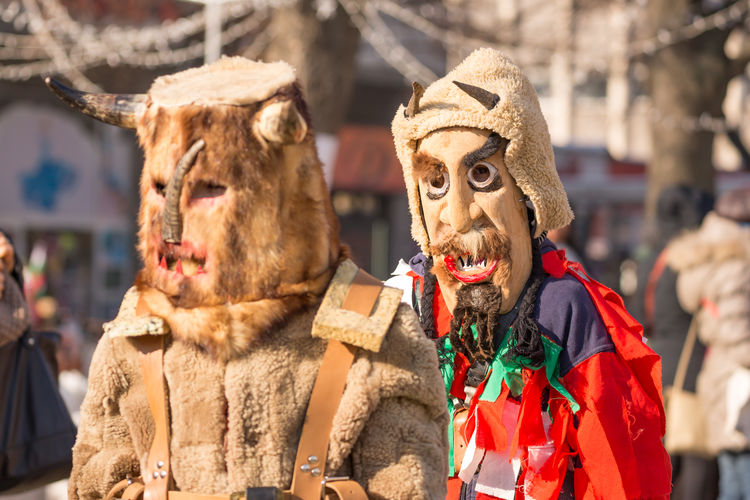 PERNIK, BULGARIA - JANUARY 26, 2018: Two dancers called kukers march and one of them looks in camera at ritual at the annual International Festival of Masquerade Games Surva in Pernik, Bulgaria Festival Season KuKer Kukeri Kukeri, Bulgaria Pernik Animal Themes Bulgaria Close-up Colorful Culture Day Festival Festivals Focus On Foreground Mammal March Marching No People Outdoors Participants Surva Survakar