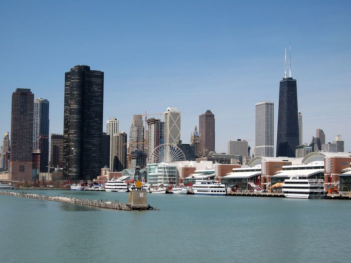 Modern Skyscrapers By Lake Michigan In City Against Clear Blue Sky