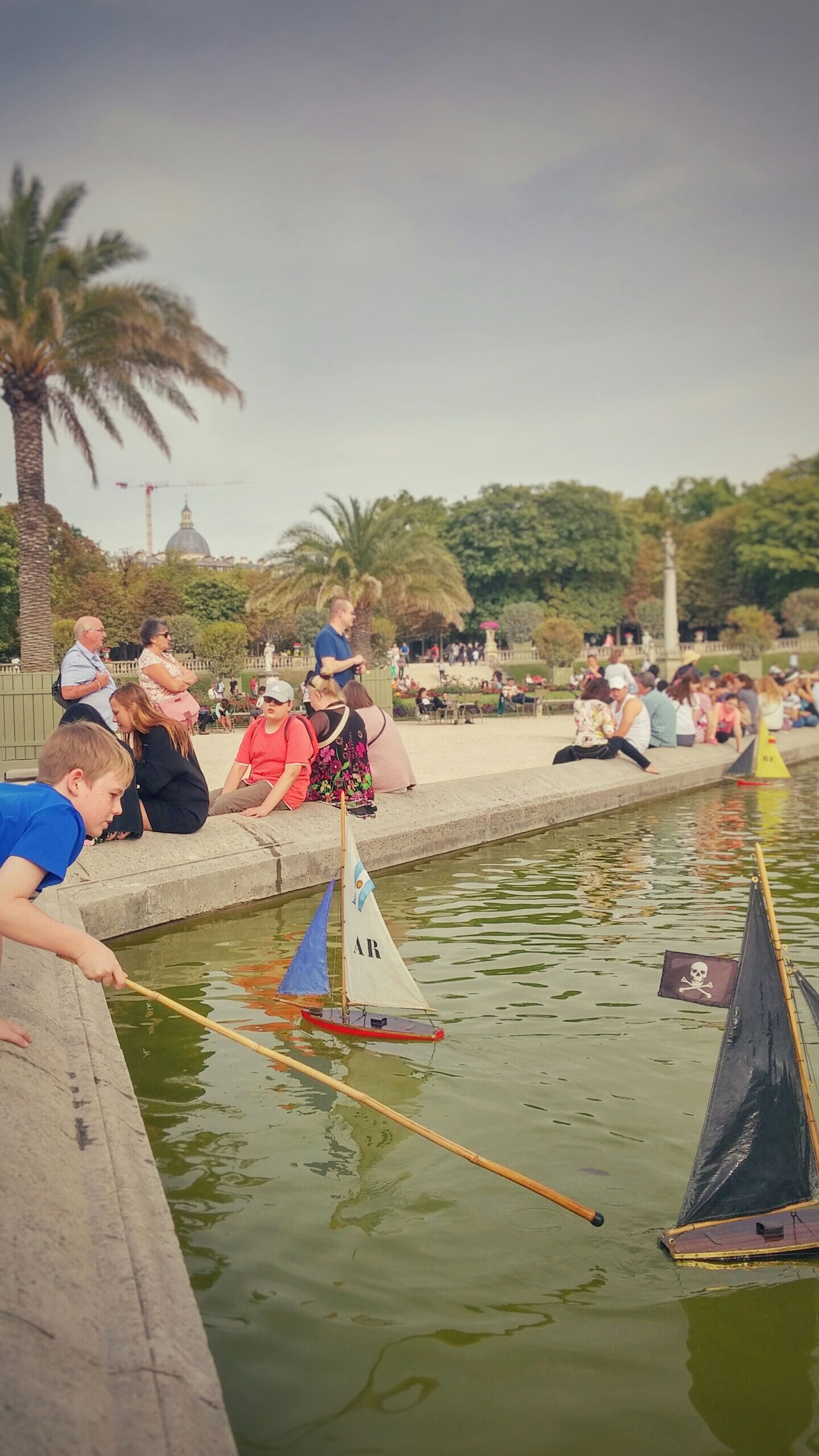 water, lifestyles, leisure activity, men, beach, person, sea, tree, nautical vessel, large group of people, vacations, palm tree, boat, tourist, sky, transportation, relaxation, tourism, shore